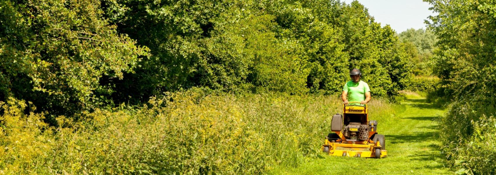arbeider staand op grasmachine