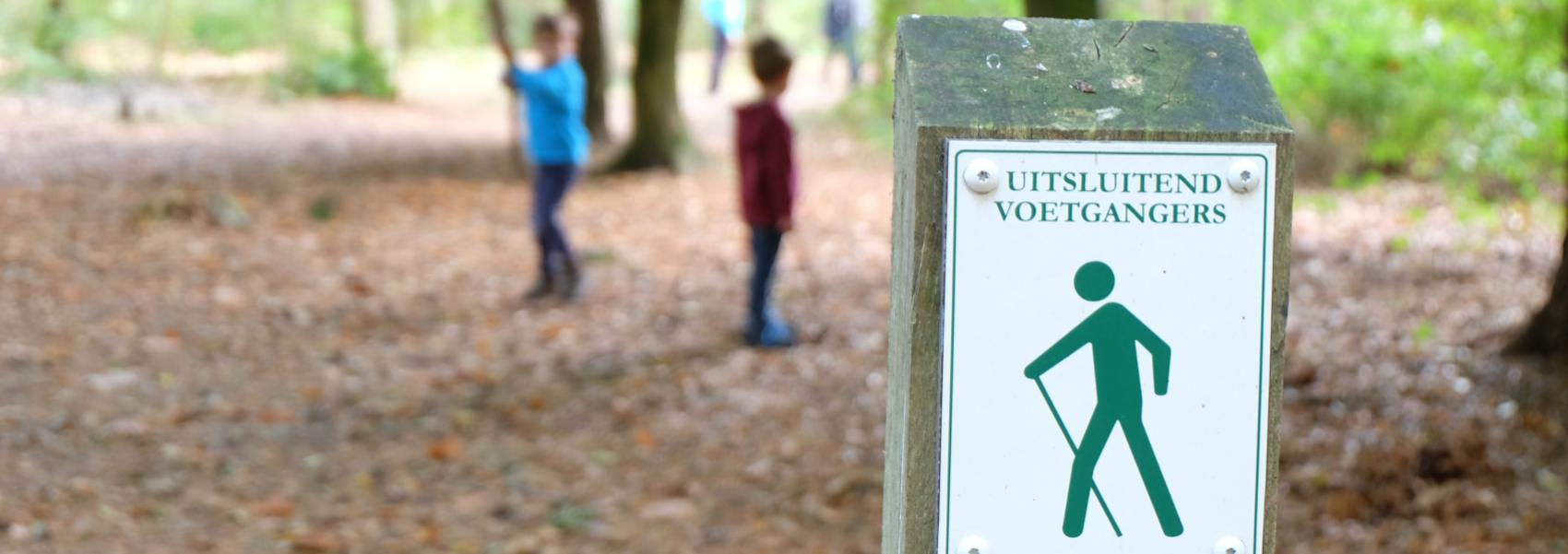 wandelbordje naast kinderen op het wandelpad