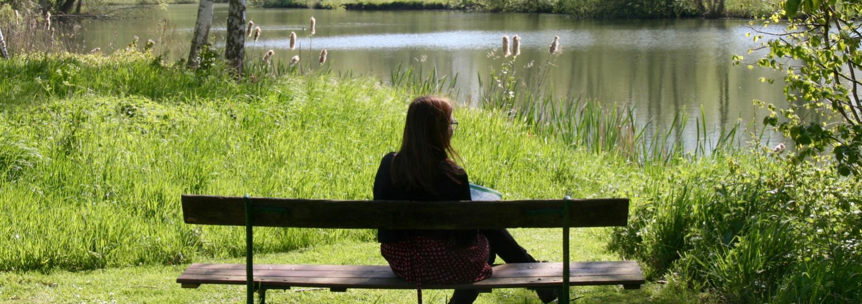vrouw op bank die kijkt naar het water