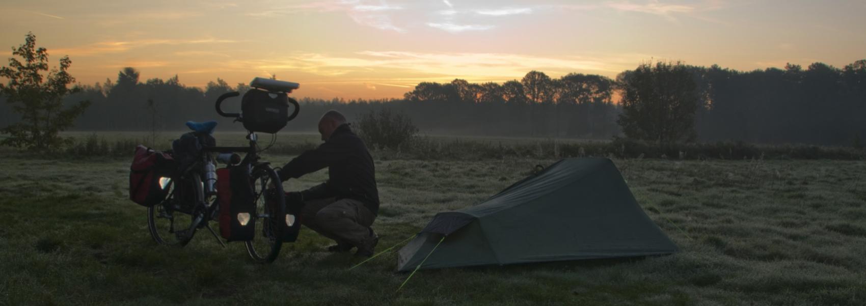 fietser bij zijn tent bij zonsondergang