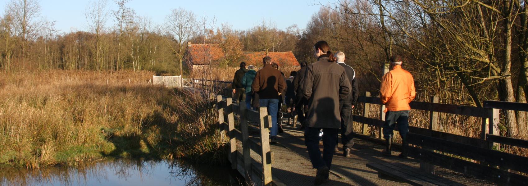 wandelaars op een brugje over het water