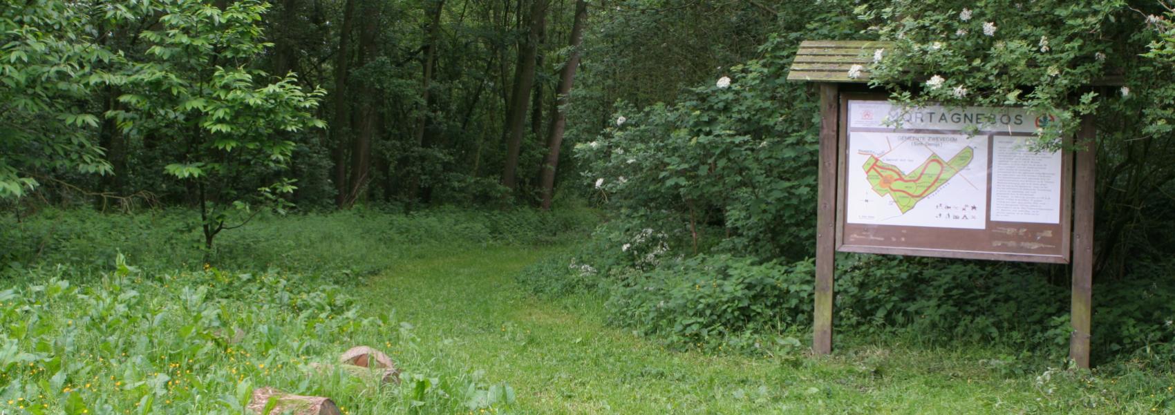 zicht op het landschap en een onthaalbord van het mortagnebos